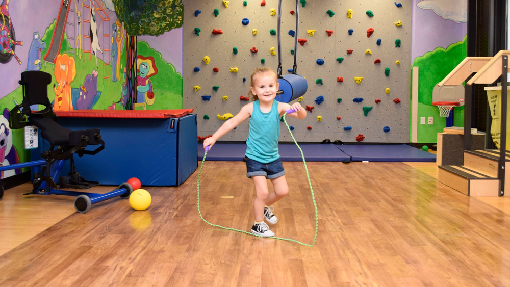 Child jumping rope in gym area