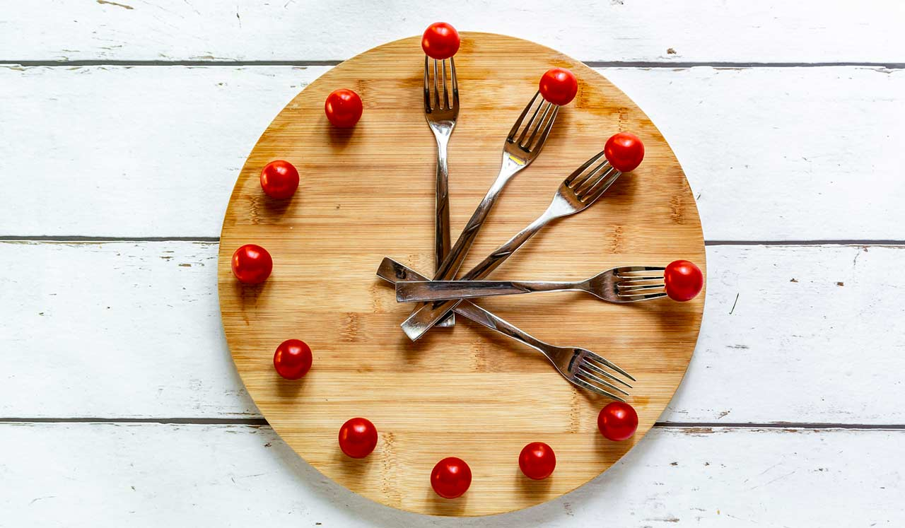 A plate with forks and tomatoes decorated like a clockface.
