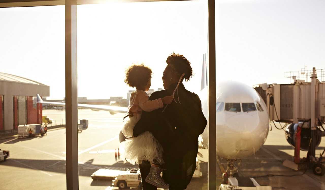 A person holding a child looking at an airplane at the airport.