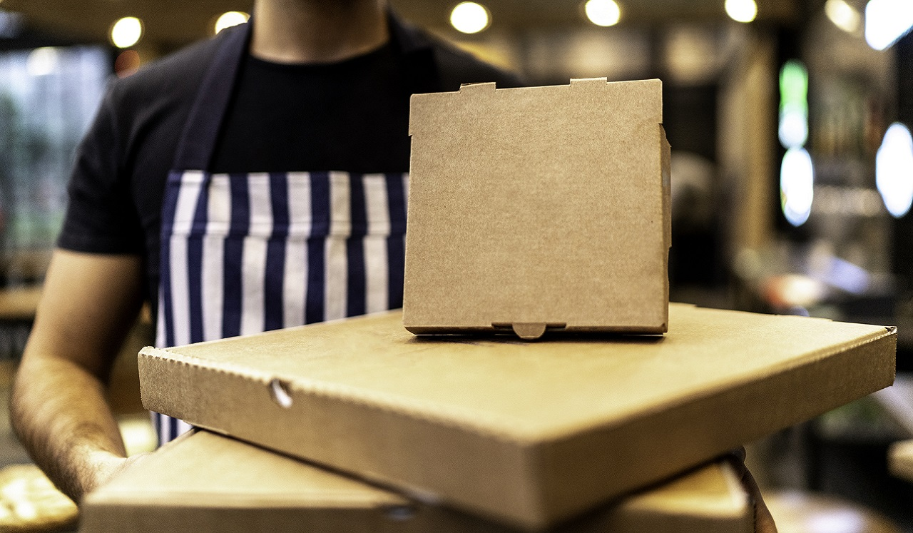 An assortment of take-out food boxes being held by a person donning a striped apron.