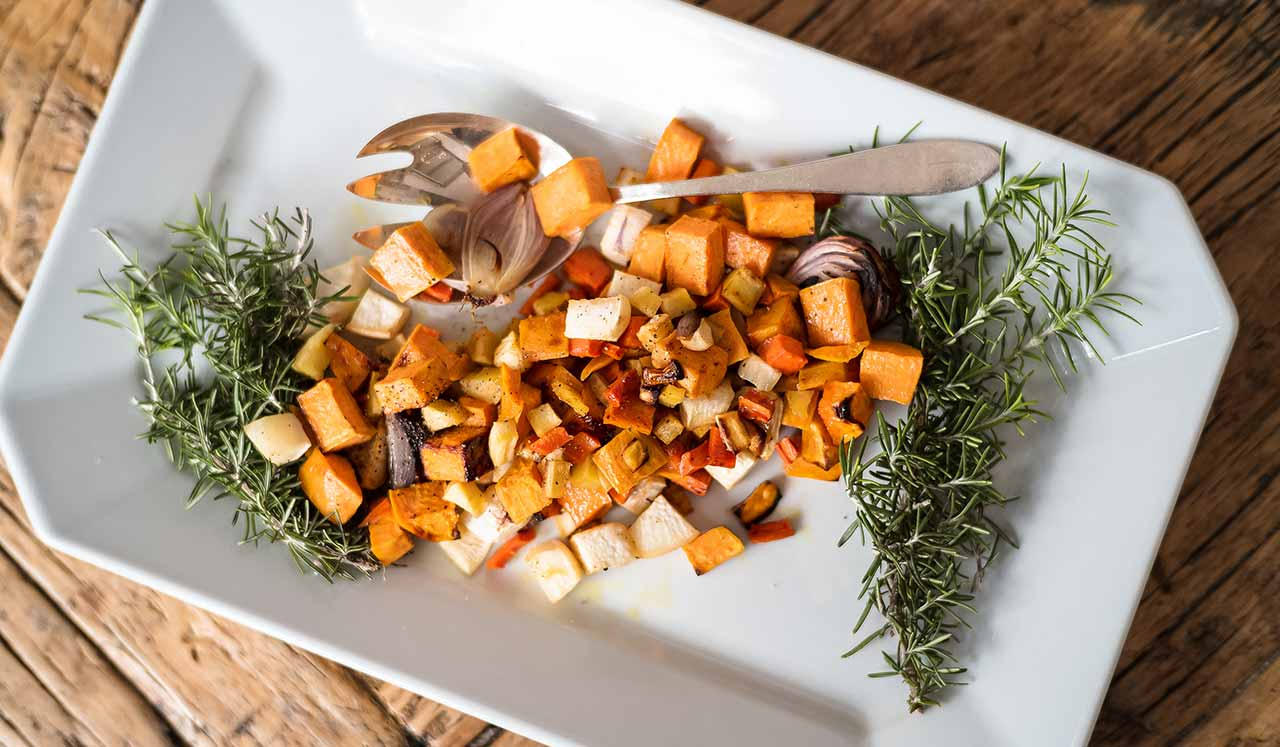 A rectangular plate with an assortment of roasted root vegetables.