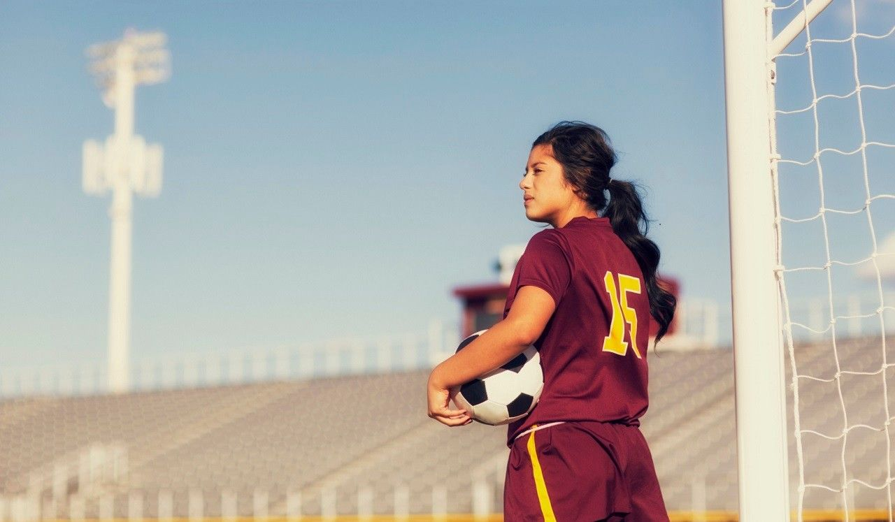 A teenage girl in a sports uniform holding a soccer ball.