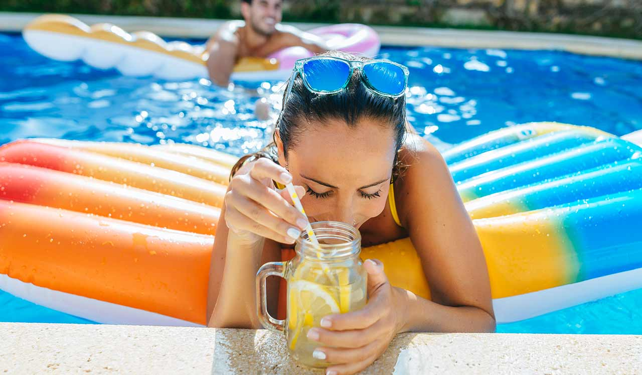 A woman on a colorful raft in a pool, sips from a mason jar.