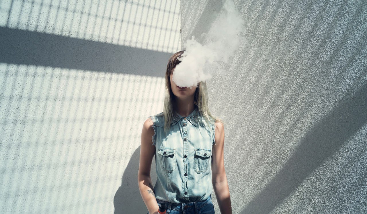 A teenage girl with smoke leaving her mouth and obscuring her face.