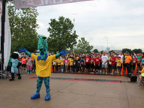Topper stands in front of racers at Run for the Rose