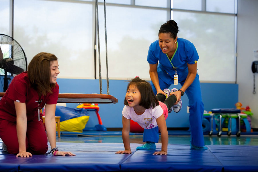 Girl participating in rehabilitation with therapists