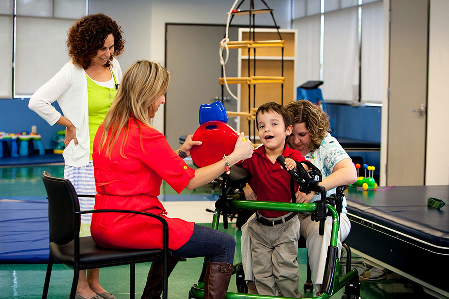 Boy participating in rehabilitation with physician and therapists