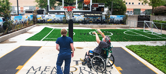 A TIRR Memorial Hermann patient and therapist play basketball as a means of rehabilitation