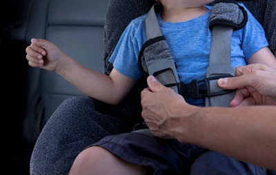 Adult buckling a child into a car seat
