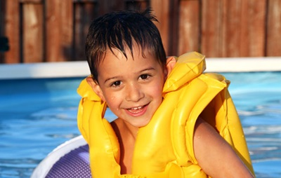Child wearing a life jacket in a pool