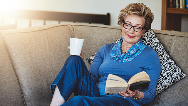 A senior woman relaxes on the couch with a book and coffee in hand.