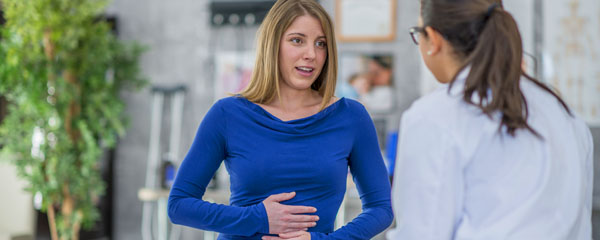 Patient holding stomach talking to doctor