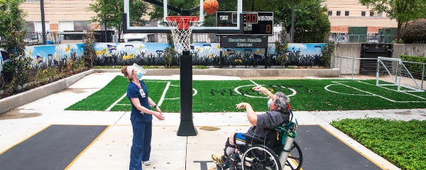 Therapist and patient playing basketball in the sports park as part of therapy